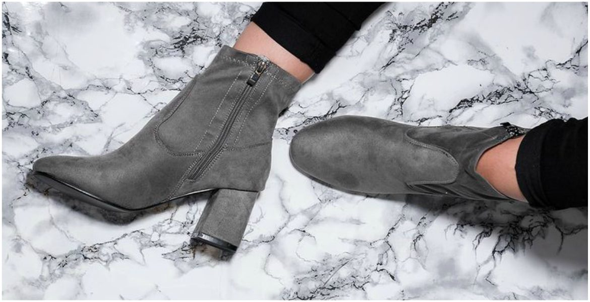 Grey ankle boots and black jeans on marble surface
