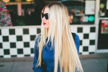 Barefoot Blonde Blogger shows off her long blonde hair extensions, paired with a blue coat, sunglasses, and slick of red lipstick.