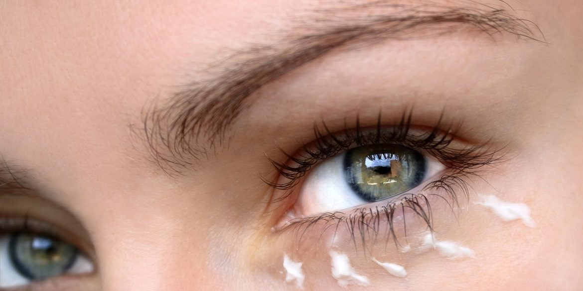 Woman with eye cream dabbed beneath her eye