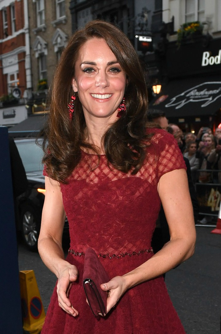 Kate Middleton showcases her classic style with a red lace dress and complementary velvet clutch bag