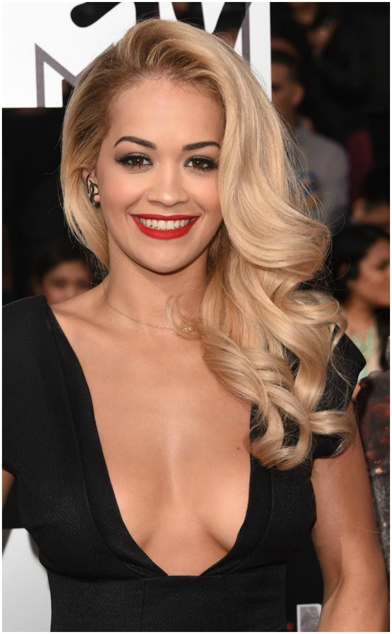 Rita Ora with glamorous side parting and black low cut dress