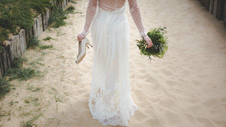 Bride walking on sand- wedding dress
