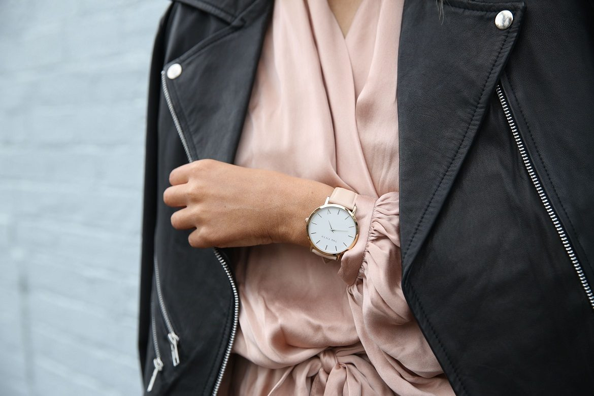 woman wearing black leather jacket with blush satin top and gold watch