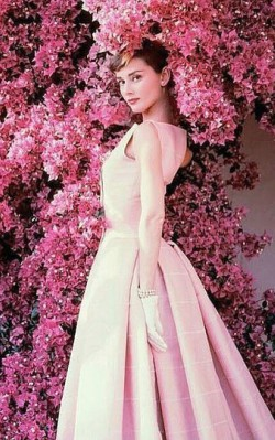 Audrey Hepburn semi formal style pink dress with white gloves, earrings and bracelet in front of pink flowers - shop the look